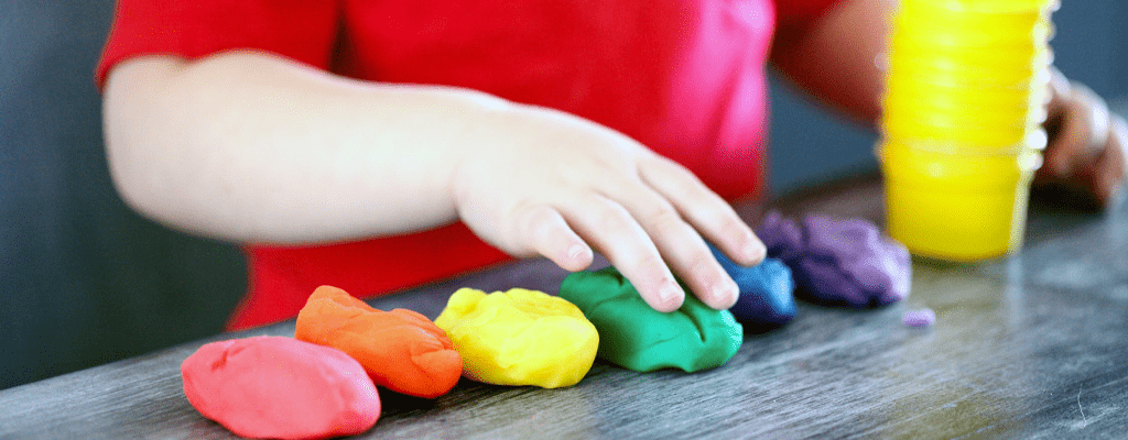 child playing with different colored doughs