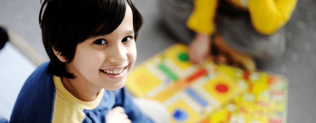 child smiling while learning more words through scrabble
