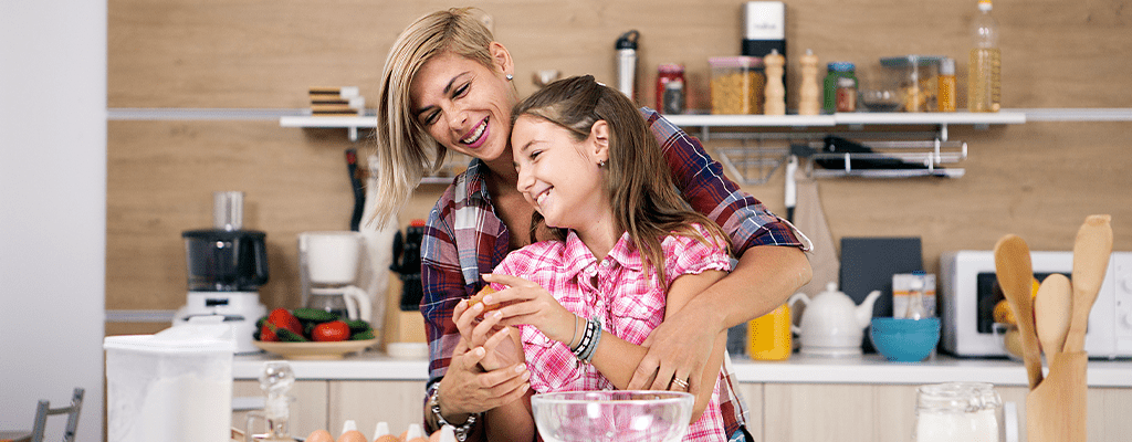 child learning to cook with her mother during quarantine