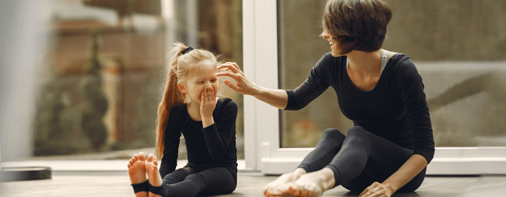Mother and daughter doing light exercises to refresh mind from online learning
